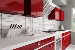 Gloss red kitchen units with white worktop and tiled splashback